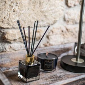 αρωματικό χώρου μέσα σε ξύλινο δίσκο και από πίσω ένα μαύρο κερί