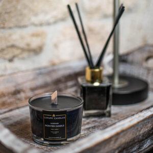 εδώ βλέπετε ένα μαύρο κερί με ξύλινο φυτίλι μέσα σε ένα ξύλινο δίσκο και από πίσω του ένα αρωματικό χώρου μαύρη βανίλια