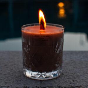 κερί whiskey and caramel σε κρυστάλλινο ποτήρι χρώματος μπεζ με ξύλινο φυτίλι, αναμμένο